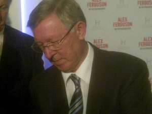 Sir Alex Ferguson signs autographs for a group of Chinese journalists at the event in central London
